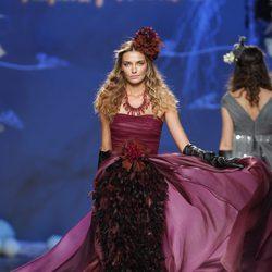 Desfile de Francis Montesinos en la Fashion Week Madrid: vestido largo burdeos con plumas del mismo tono