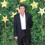 Antonio Banderas con traje negro desabrochado y camisa blanca informal