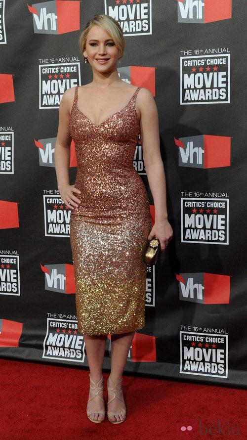 Jennifer Lawrence con vestido brillante y clutch dorado