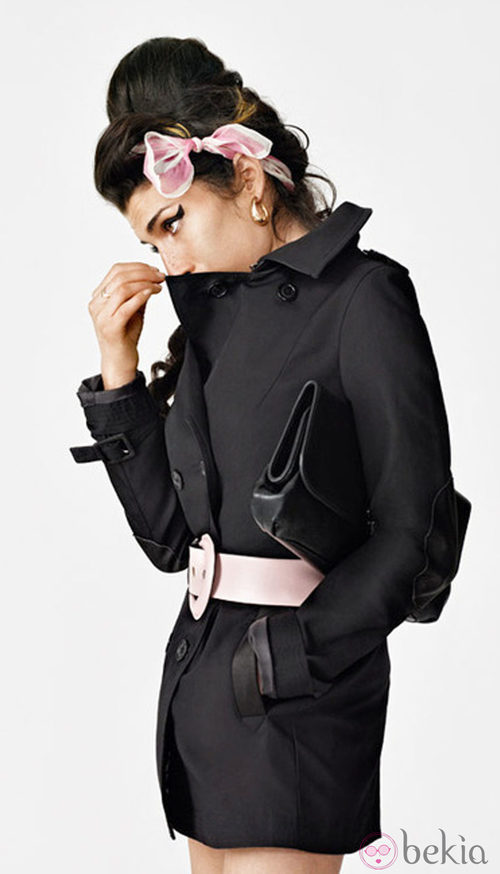 Amy Winehouse con un abrigo negro y lazo rosa para Fred Perry