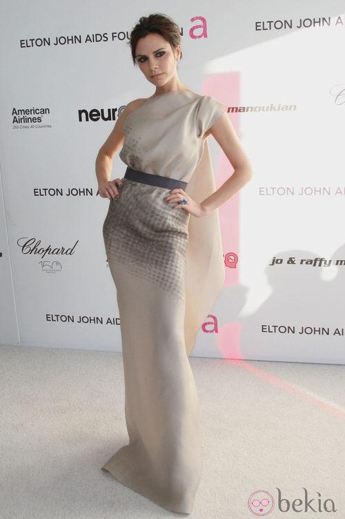 Victoria Beckham con un vestido de su firma largo y dorado