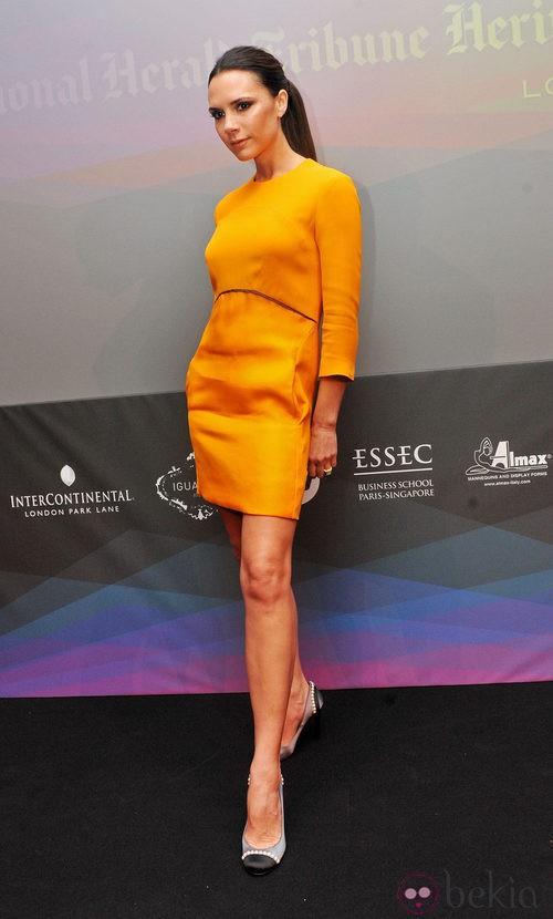 Victoria Beckham con un vestido de su firma naranja