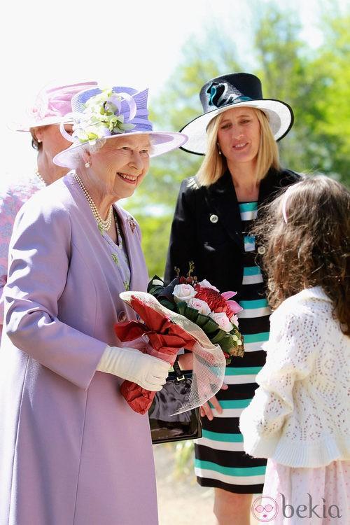 La Reina Isabel II con un conjunto violeta y sombrero en el mismo color