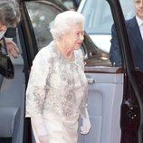 La Reina Isabel II de Inglaterra con traje en blanco roto y chaqueta con detalles plateados