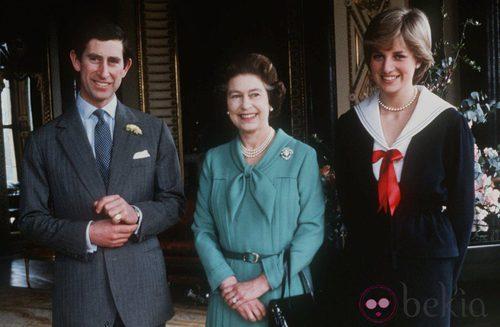 La Reina Isabel II de Inglaterra con un vestido azul turquesa con lazada en el cuello