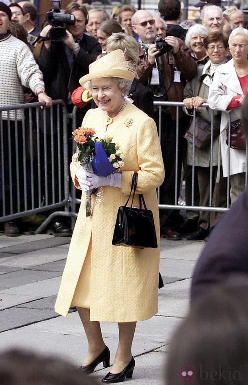 La Reina Isabel II de Inglaterra con un vestido primaveral en color amarillo de Angela Kelly