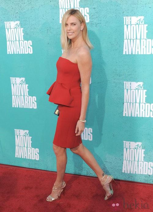 Charlize Theron con un vestido rojo silueta peplum en la alfombra roja de los MTV Movie Awards 2012