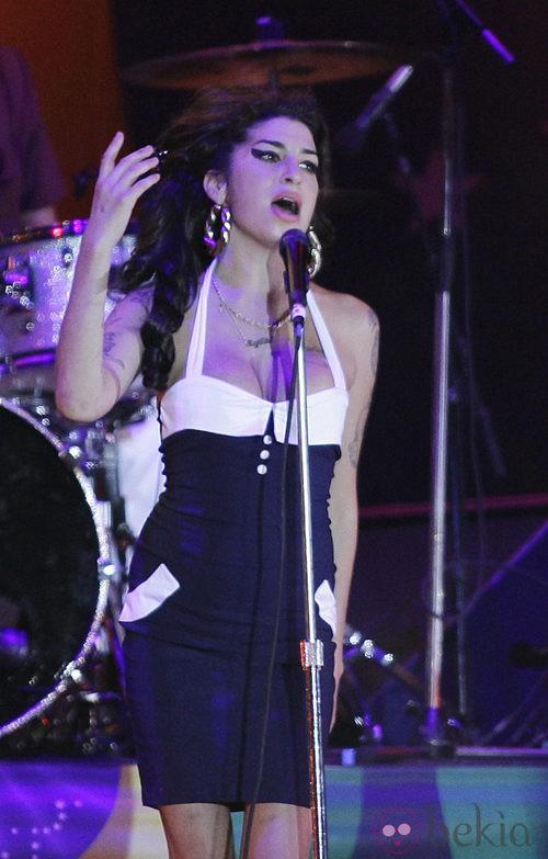 Amy Winehouse con un vestido blanco y negro en un concierto