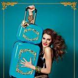 Anna Dello Russo posando con dos maletas de su colección para H&M