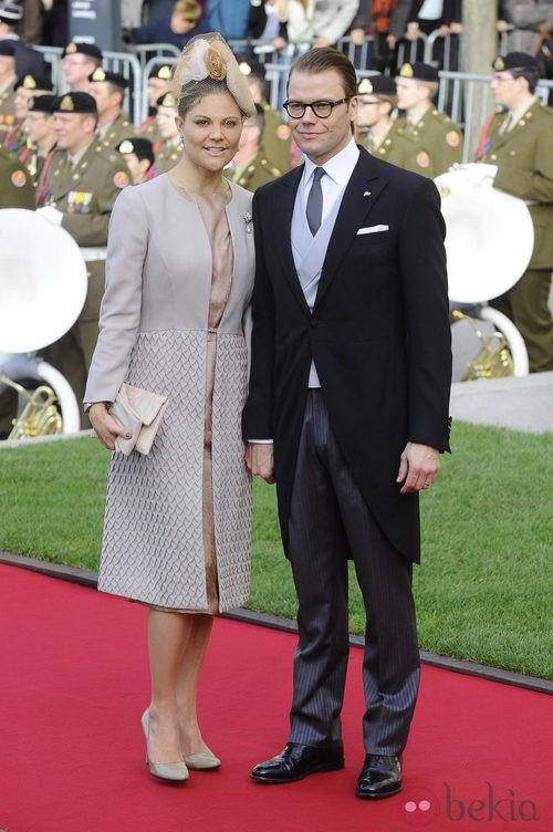 Victoria de Suecia con abrigo girs con detalles plisados en la boda de Guillermo y Stéphanie de Luxemburgo