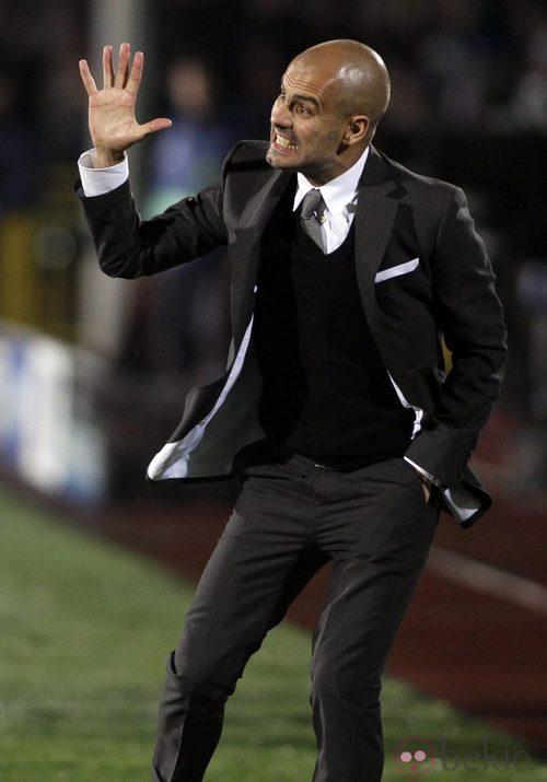 Guardiola con traje durante un partido