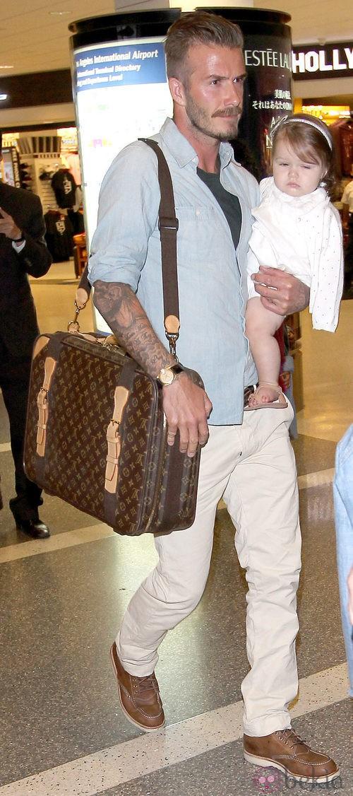David Beckham con un pantalón de color crema, camisa azul y cartera de Louis Vuitton