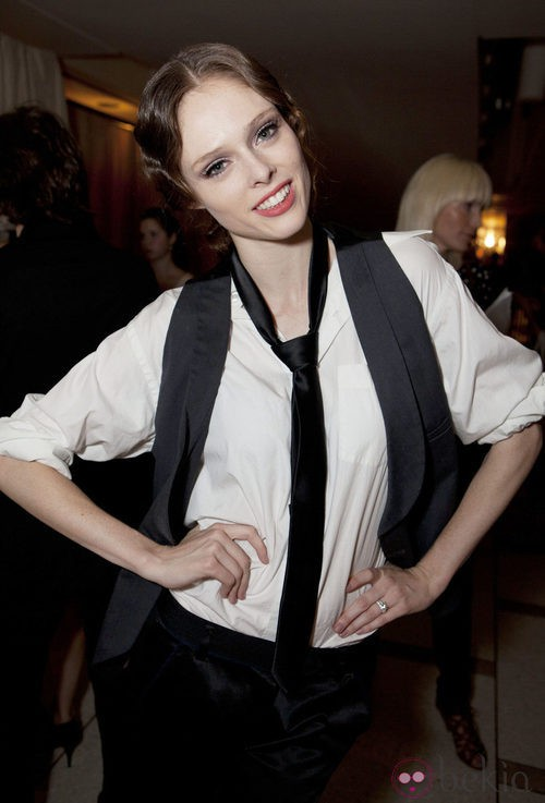 Coco Rocha con un traje de camisa blanca y chaqueta y corbata negras