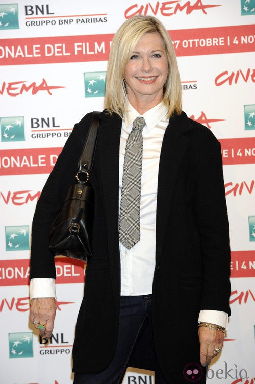 Olivia Newton-John con un traje masculino de chaqueta y corbata