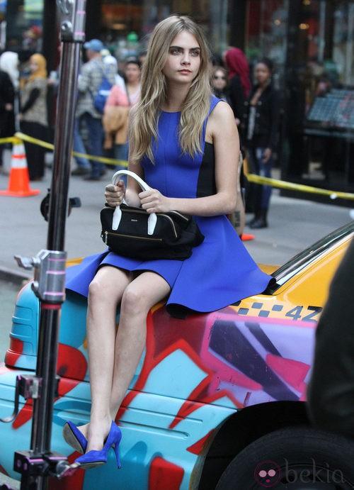 Cara Delevingne con un vestido azul durante el shooting de la campaña primavera/verano 2014 de DKNY