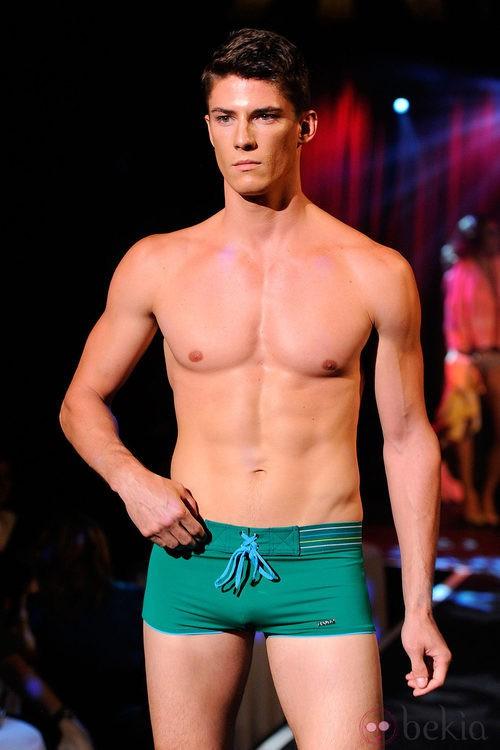 Modelo con torso desnudo y bañador verde de 2(X)ist para verano de 2012