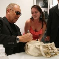 Michael Kors firma un bolso en la Vogue Fashion's Night Out de Nueva York