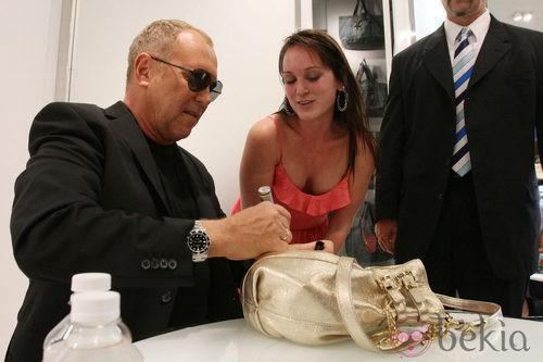Michael Kors firma un bolso en la Vogue Fashion's Night Out de Nueva York
