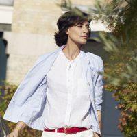 Inès de la Fressange posando para Uniqlo con un conjunto de blusa y pantalón blanco