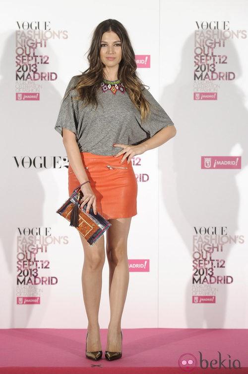 Úrsula Corberó con falda de cuero naranja y blusa gris con abalorios