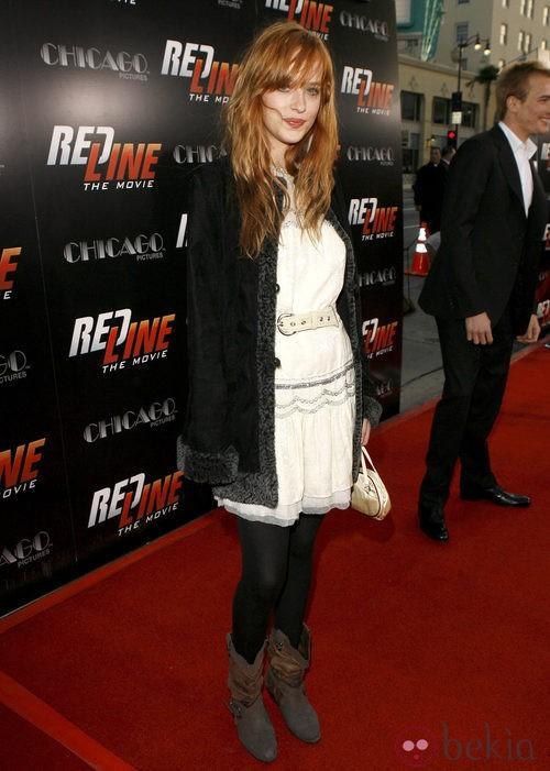 Dakota Johnson con vestido blanco roto y botines marrones en una premiere