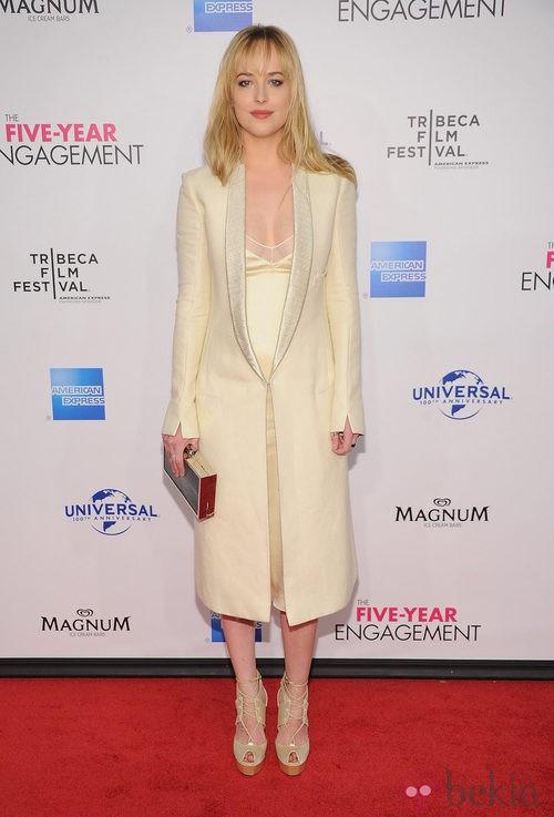 Dakota Johnson con un look de vestido y abrigo blanco roto