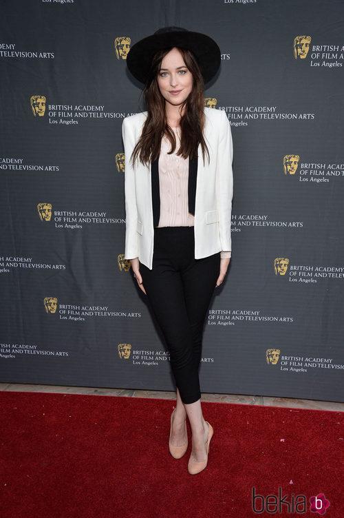 Dakota Johnson con un pantalón midi negro y sombrero también negro