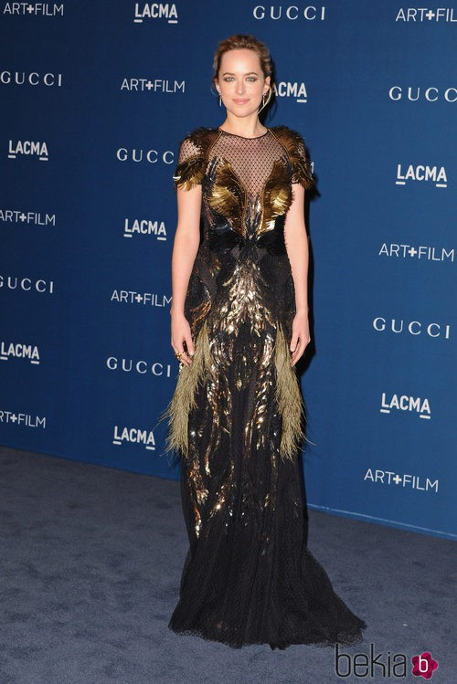 Dakota Johnson con un vestido dorado con plumas