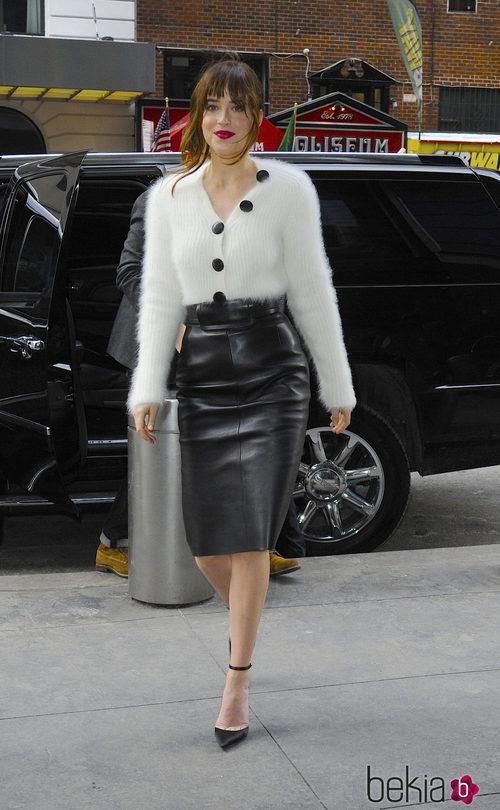 Dakota Johnson con una falda de cuero negra y chaqueta de pelo blanca