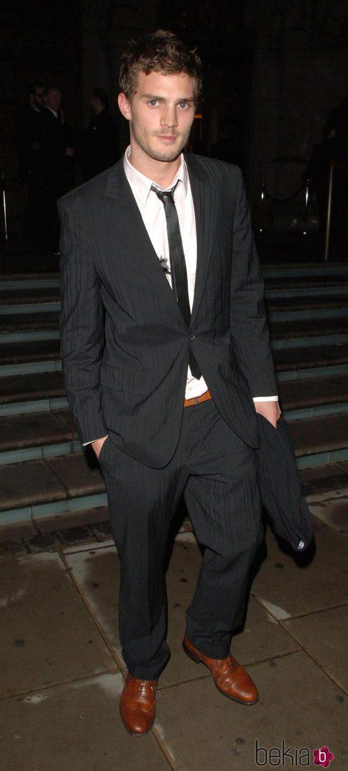 Jamie Dornan con traje negro, camisa blanca y corbata estrecha