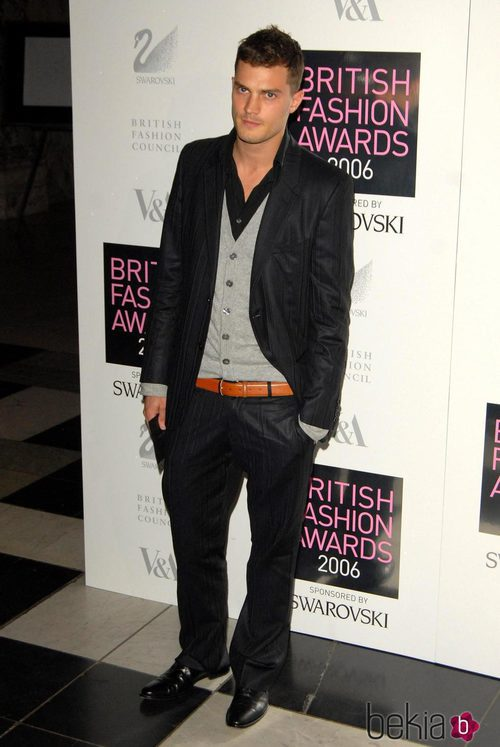 Jamie Dornan con chaqueta negra y cardigan gris