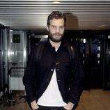 Jamie Dornan con chaqueta negra, camiseta blanca y vaqueros