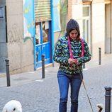 Adriana Ugarte con vaqueros y abrigo de colores paseando a sus perros