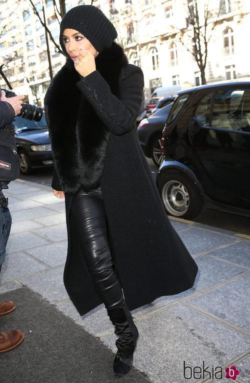 Kim Kardashian llegando a París con pantalón de cuero, abrigo negro y gorro de lana
