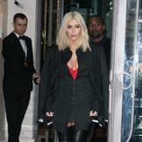 Kim Kardashian con camisa a rayas, camiseta roja y botas en la Paris Fashion Week