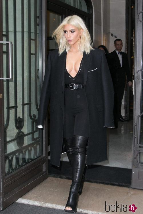 Kim Kardashian con abrigo, jumsuit y botas en negro en la Paris Fashion Week