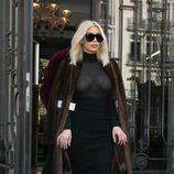 Kim Kardashian con un vestido de transparencias negro y un abrigo marrón en la Paris Fashion week