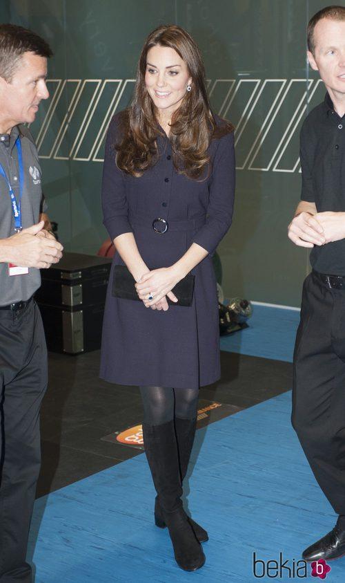 Kate Middleton con un vestido azul oscuro y botas altas negras