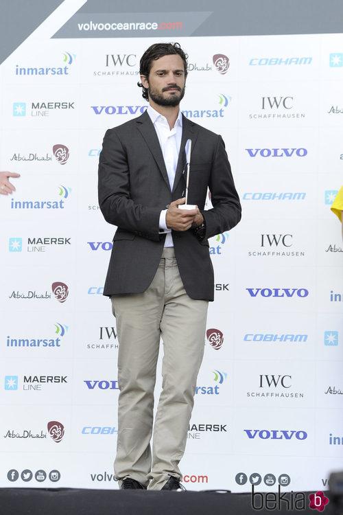 Carlos Felipe de Suecia con americana gris, camisa blanca y pantalones chinos en blanco roto