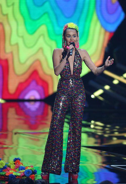 Miley Cyrus con un jumpsuit de lentejuelas multicolor y diadema neón en los VMA 2015
