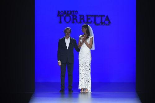 Roberto Torretta junto con una de las modelos tras la presentación de su nueva colección primavera/verano 2016 en Madrid Fashion Week