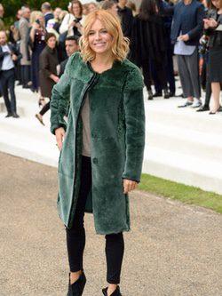 Sienna Miller con abrigo verde y pantalón pitillo negro en el desfile de Burberry en la London Fashion Week