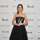 Marion Cotillard con vestido negro sujetando premio a la mujer del año de Harper