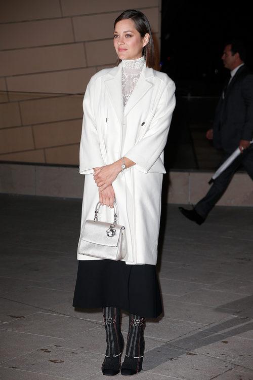 Marion Cotillard con gabardina blanca y falda negra en la inauguración de la fundación Louis Vouitton en 2014