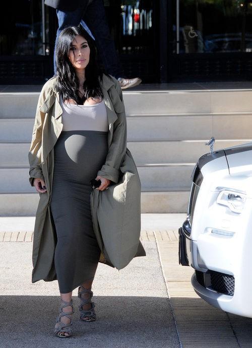 Kim Kardashian con vestido blanco y gris y gabardina larga en su segundo embarazo