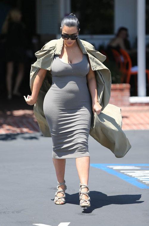 Kim Kardashian con vestido gris y gabardina en su segundo embarazo