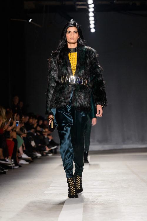 Modelo con abrigo negro y pantalón azulado en el desfile de Balmain para H&M en Nueva York