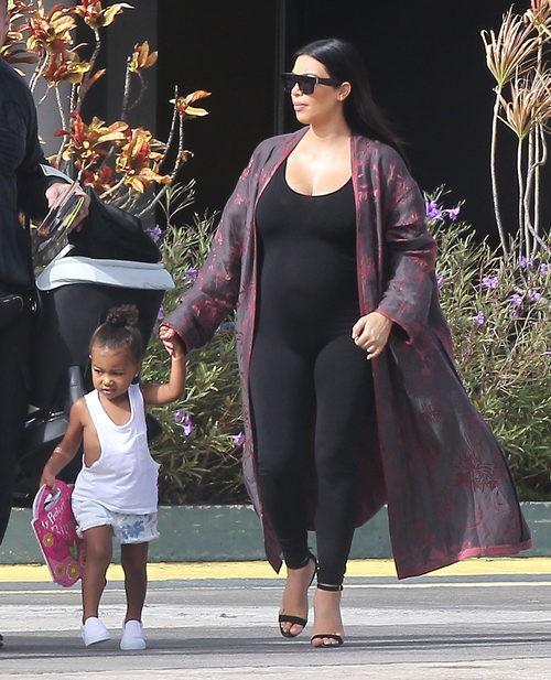 Kim Kardashian con ajustado jumpsuit negro y kimono granate en su segundo embarazo