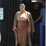 Kim Kardashian con vestido y abrigo en tonos tierra en su segundo embarazo