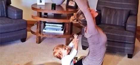 Gisele Bündchen con mallas azul marino y camiseta lila haciendo yoga con su hija Vivian
